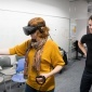 Andrea Stevenson Won, assistant professor of communication and director of the Virtual Embodiment Lab, uses a virtual reality simulator.